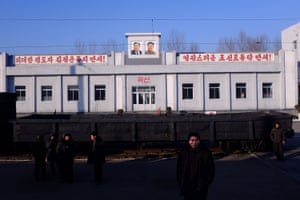 Passengers brave the winter on a railway platform on the Sinuiju-Pyongyang line under the watchful eye of the country's two former leaders