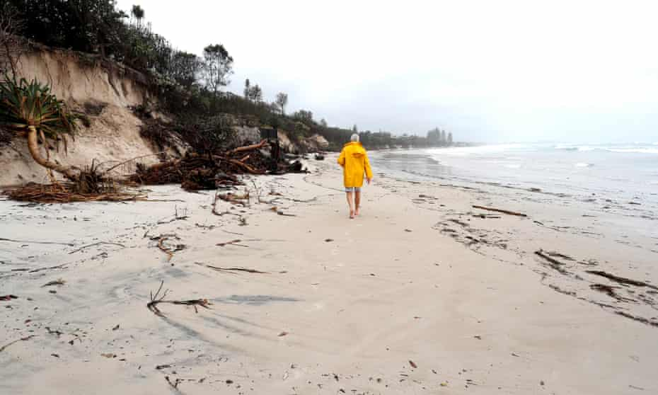A man walks along a heavily eroded section of beach in Byron Bay.