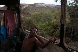 Venezuelan Hildemaro Ortiz relaxes inside of an abandoned bus in the border city of Pacaraima.