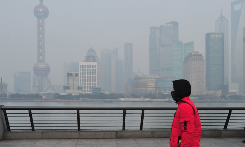 A tourist wearing a face mask against air pollution visits the Bund along the river Huangpu in heavy smog in Shanghai, China.