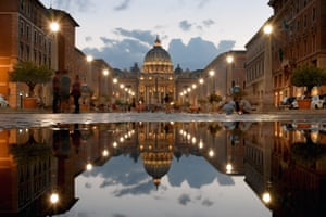 Rome, Italy: St Peter's Basilica reflected in a puddle as tourists walk along the Via della Conciliazione