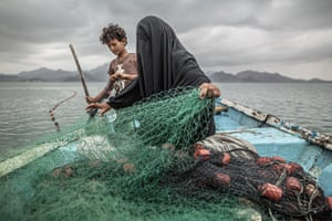 Fatima and her son prepare a fishing net on a boat in Khor Omeira bay, Yemen