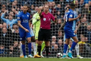 Referee Robert Madley gestures towards Leicester City's Riyad Mahrez to explain why he's disallowed the goal.