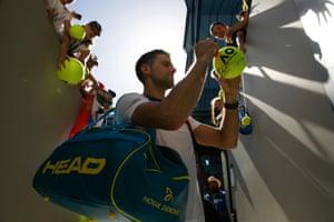 Novak Djokovic signs autographs for the crowd.