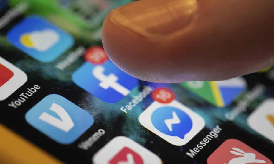 A fingertip selecting the Facebook app on a smartphone