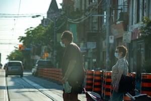 People cross the street in Toronto on Monday.