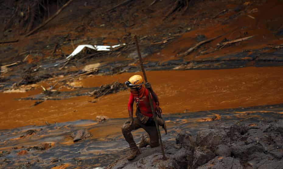 A rescue worker searches for victims next to a river of mud