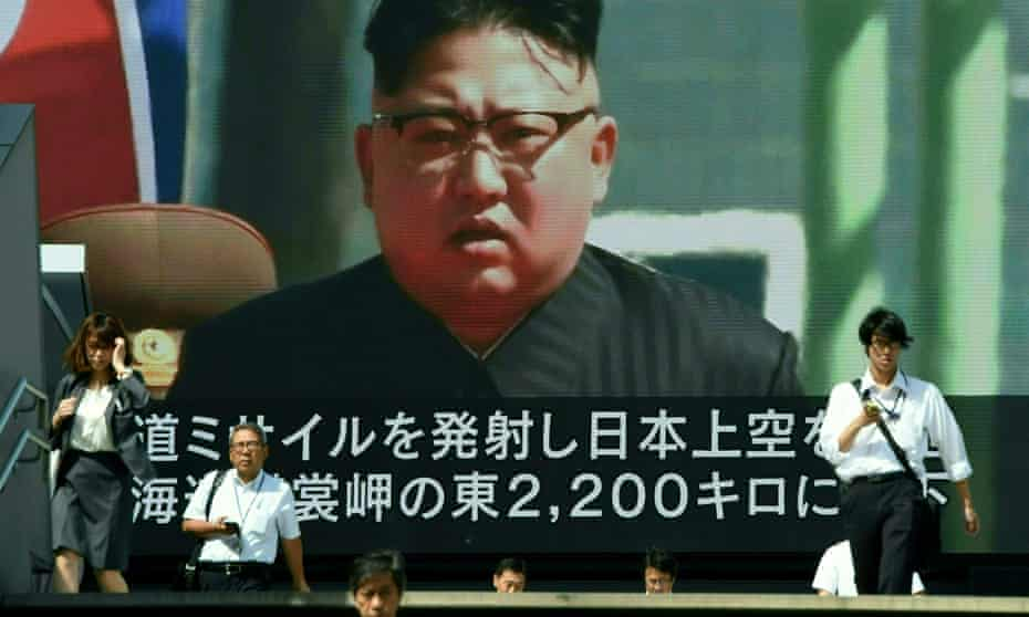 Pedestrians walk in front of a large video screen in Tokyo broadcasting a news report showing the North Korean leader Kim Jong-Un