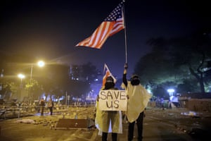 Demonstrators hold aloft US and UK flags near the campus in a plea for international help