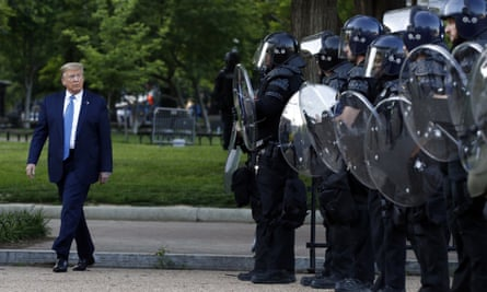 President Donald Trump walks past police in Lafayette Park after posing with a Bible outside St John's Church across from the White House on 1 June 2020.