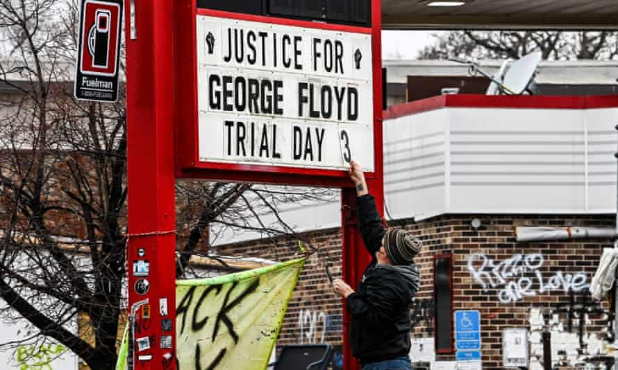 A man changes the number of a sign board at a makeshift memorial of George Floyd before the third day of jury selection begins in the trial of former Minneapolis police officer Derek Chauvin who is accused of killing Floyd, in Minneapolis, Minnesota on Wednesday.