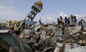 Villagers walk through the wreckage of Palu on the Indonesian island of Sulawesi after last month's tsunami and earthquake.