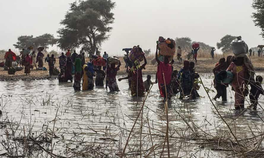 People who fled the Nigerian town of Rann after an attack by Boko Haram cross a river to seek shelter in Bodo, Cameroon