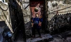 A Palestinian child keeps up the ball in front of his family's home in the Shati refugee camp, Gaza City