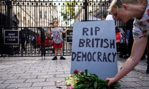 A protester lays flowers in front of a mock tombstone outside the gates of No 10 Downing Street in London.