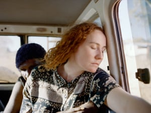 A women leaning her head on the side of a car window