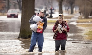 Anthony Thomson and Melody Walton make their way out of a flooded neighborhood 17 March 2019, in Fremont.