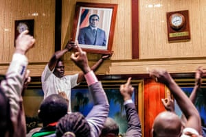 A portrait of Robert Mugabe is removed from a wall at the International Conference Centre. Parliament was sitting in the building when the president's resignation was announced