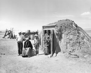 A Navajo family stands outside their hogan, a traditional dwelling, along the south rim of the Grand Canyon.