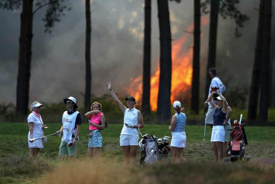 Sophie Powell, Cara Gainer, Gabriella Cowley and their caddies look on as a fire nears the 10th hole during day three of the Rose Ladies Series on the West Course in the first ladies' professional event at Wentworth.