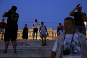 People walk on Syntagma Square in front of the Greek parliament in central Athens, Thursday, June 25, 2015. EU leaders met in Brussels for an EU summit to discuss, among other issues, migration and the Greek bailout. (AP Photo/Petros Karadjias)