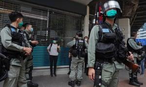 Riot police check a pedestrian in Causeway Bay, Hong Kong