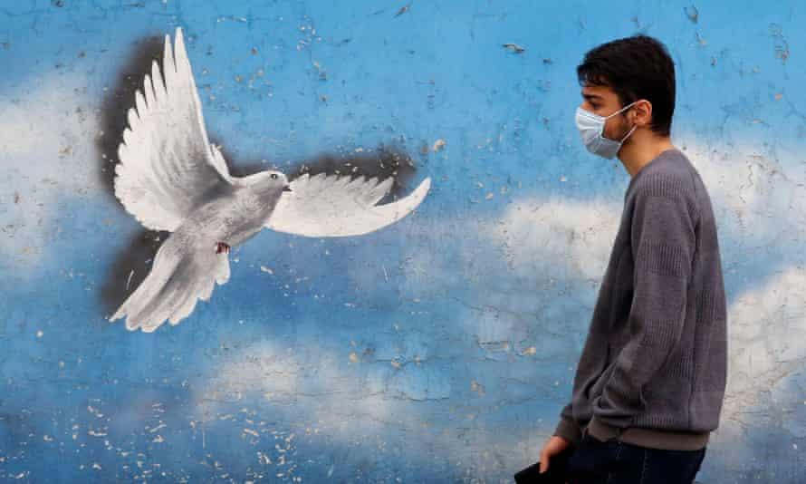 An Iranian wearing a face mask walks past a mural in a street in Tehran