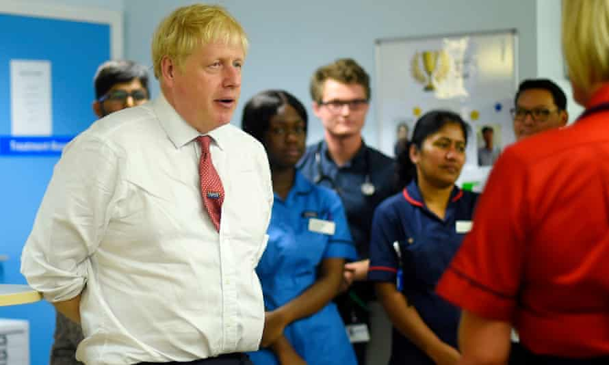 Boris Johnson speaks to medical staff during his visit to Watford general hospital in July