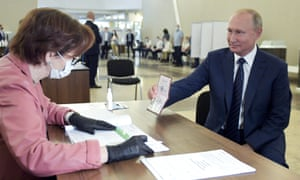 Russian president Vladimir Putin shows his passport as he arrives to vote at a polling station in Moscow. The vote was on constitutional amendments that would enable him to serve two more six-year terms.