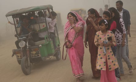 Pedestrians walk in heavy dust and smog in New Delhi at the weekend.