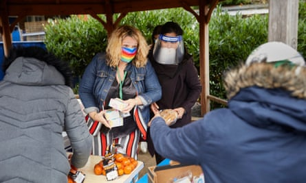 The headteacher of Mora primary school, Kate Bass, wears a rainbow mask as she hands out meals to parents at the school in Cricklewood, north London.