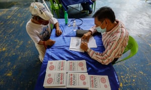 A doctor writes a prescription for human-grade capsules of the drug Ivermectin for a citizen during a free distribution campaign in Quezon City, metro Manila, Philippines.