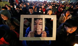 A South Korean wears a Park Geun-hye behind bars-mask while attending a candlelight rally against the president in Seoul.