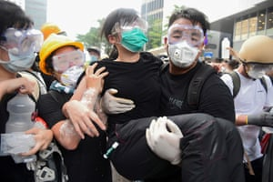Protesters try and protect themselves against teargas fired by police