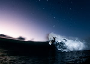 A surfer rides a wave at night