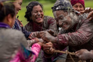 Farmers play tug of war in a paddy field on National Paddy Day in Tokha village, on the outskirt of capital Kathmandu, Nepal