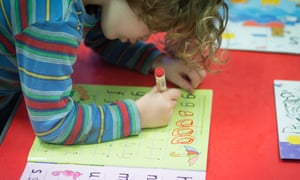 A young girl writes letters at a playgroup for pre-school aged children