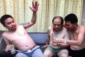 Vixay Keosavang (centre) pictured shirtless and on holiday with the Bach brothers, 'Boonchai' and Van Limh