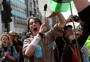 A climate change activist bangs a drum at Oxford Circus