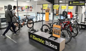 Customers wearing face masks walk past electric bikes in a Halfords store in Luton