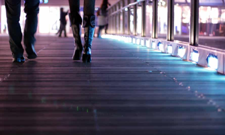 Woman's boots and a man's shoes walking across a deck at night time.