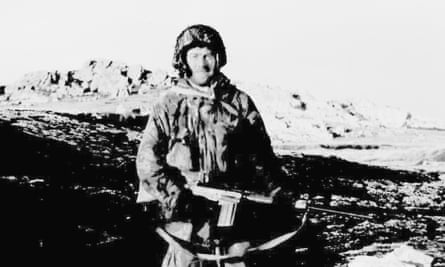 Falkland Islanders At War-P21.tif Still in battle dress and armed with a self-loading rifle, Terry Peck (the islands former police chief) stands on the slopes of Mount Longdon