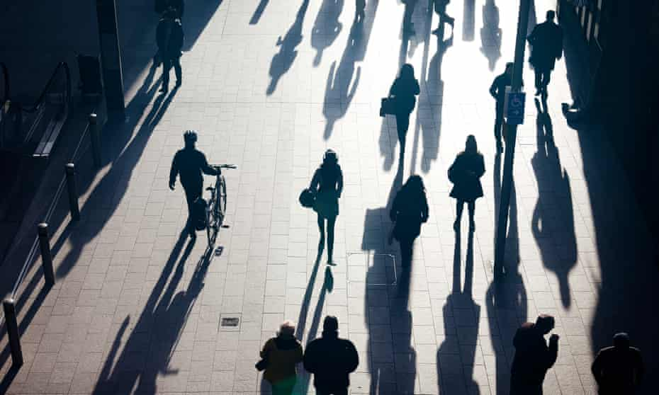 Silhouettes of people walking in the sun