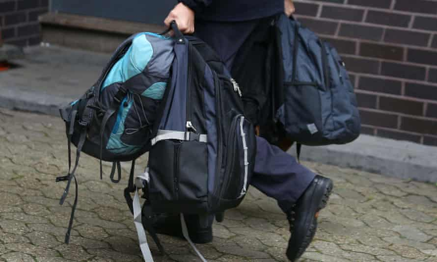 Bags are carried into an immigration centre in south London