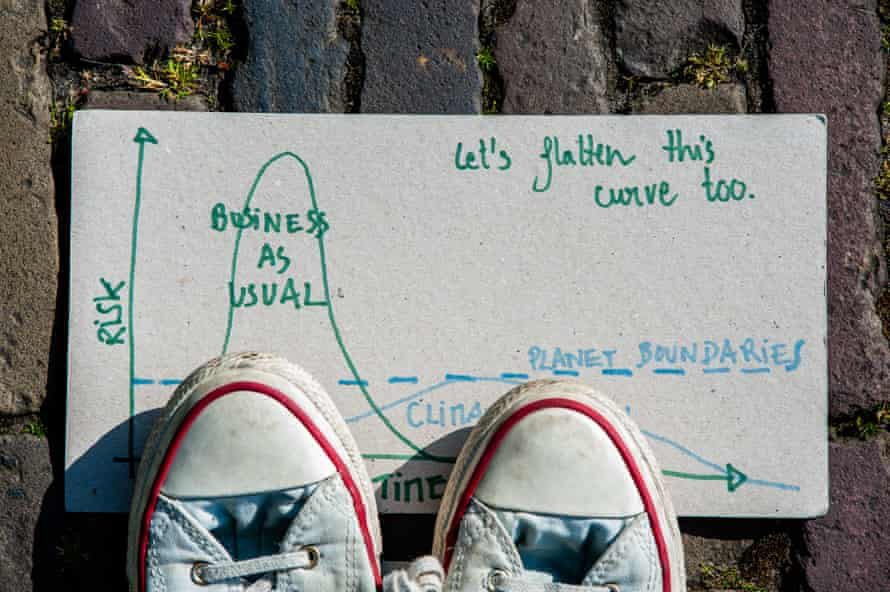 A climate placard saying 'Let's flatten this curve too' is placed on the ground under a pair of trainers