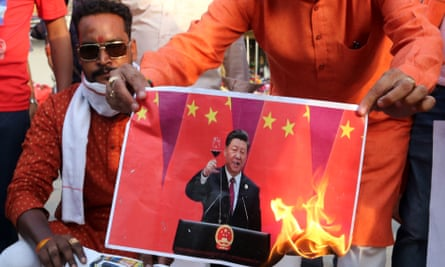 Anti-China protesters in India set alight a picture of the Chinese leader