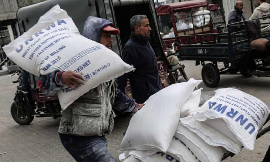 A Palestinian man carries a sack of flour after receiving food supplies at the Khan Yunis refugee camp in the southern Gaza Strip
