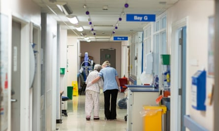 A modern hospital corridor. We can see the back of a nurse and her patient, an elderly person in pale pajamas; the nurse has her arm around the patient.
