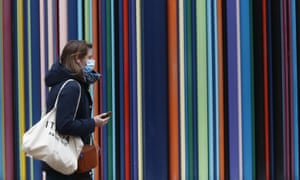 A woman wearing masks to prevent the spread of the coronavirus walk at la Defense business district in Paris, Thursday, 18 March 2021.