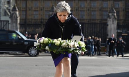 Theresa May lays a floral tribute outside parliament in London.